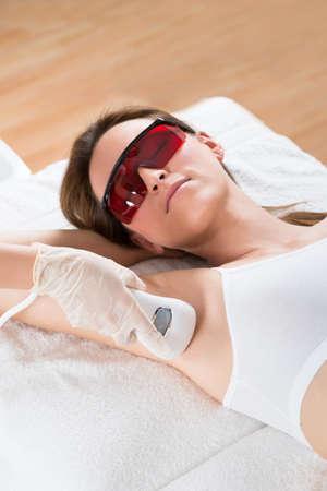 axila: Esteticista quitar el pelo de axila de la mujer joven con Depiladora