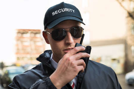 job security: Portrait Of Young Male Security Guard Talking On Walkie-talkie Stock Photo