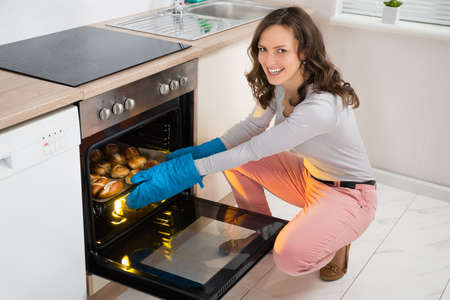 Happy Woman Baking Bread Roll In Kitchen Oven