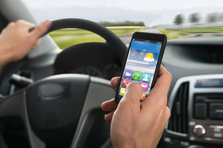 media gadget: Close-up Of A Persons Hand Using Cellphone While Driving A Car Stock Photo