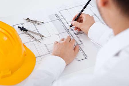 Close-up bijgesneden afbeelding van een jonge mannelijke architect werkt aan blauwdrukken verspreid op een tafel