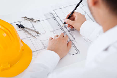 architect: Closeup cropped image of a young male architect working on blueprints spread out on a table Stock Photo
