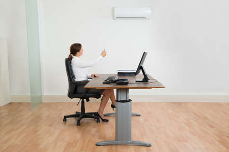office appliances: Young Businesswoman Sitting On Chair Using Air Conditioner In Office