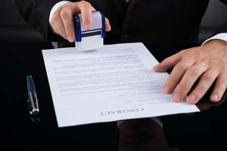 stamper: Close-up Of Businessperson Using Stamper Over Contract Paper Stock Photo