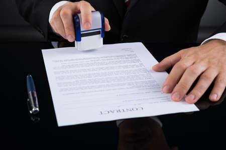 documentos: Primer Del Empresario Utilizando Stamper sobre papel Contrato Foto de archivo