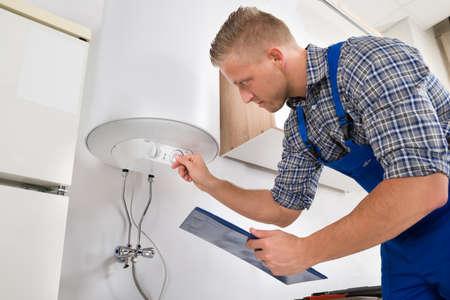 Mannelijke Werknemer Met Klembord Aanpassen temperatuur van het water Heater