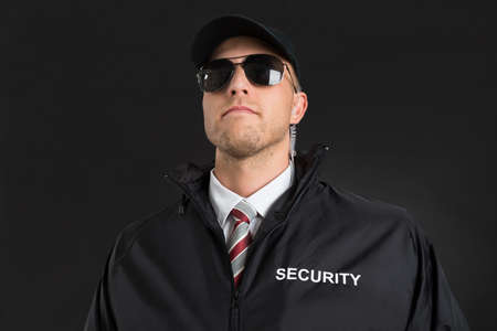 earpiece: Young Male Bodyguard Wearing Sunglasses And Earpiece Over Black Background Stock Photo