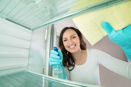 spray: Hermosa mujer de limpieza con trapo Vista desde el interior del refrigerador