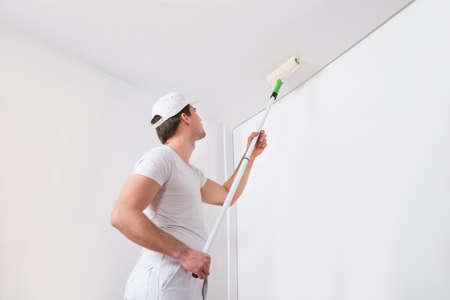 pintor de casas: Pintor joven en blanco pintura uniforme con el rodillo de pintura en la pared