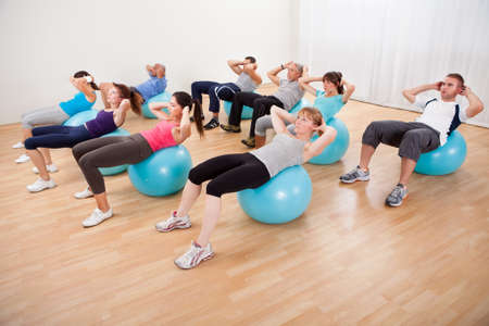 Class of diverse people doing pilates exercises in a gym doing head lifts to strengthen their abdominal muscles photo