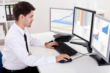 agente comercial: Sobre la opini�n del hombro de las pantallas de ordenador de un corredor de bolsa de comercio en un mercado alcista que muestra gr�ficos ascendente Foto de archivo