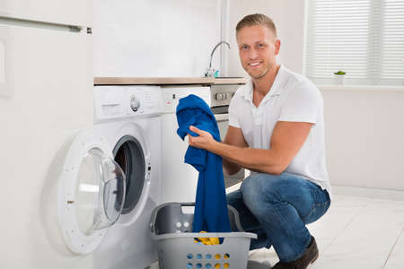 house cleaning: Man With Laundry Basket Loading Washing Machine With Clothes In Kitchen Room