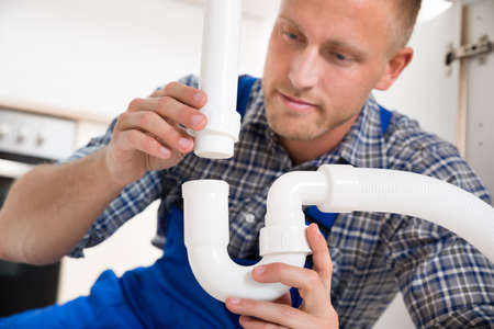 sewer pipe: Young Plumber Repairing Pipe Of Sink In Kitchen Stock Photo