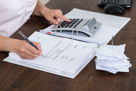 calculating: Close-up Of Accountant Calculating Receipt In Office Stock Photo
