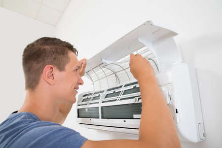 man in air: Young Happy Man Cleaning Air Conditioning System At Home Stock Photo