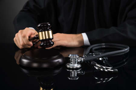 conclusive: Close-up Of Judge Hands Hitting Gavel With Stethoscope In Courtroom Stock Photo