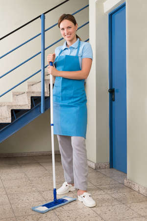 floor standing: Young Happy Female Janitor Standing With Mop In Corridor Stock Photo