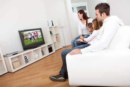 mujer viendo tv: Joven de la familia viendo la televisi�n juntos en casa Foto de archivo