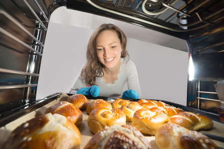 baking tray: Young Woman Removing Bun Tray View From Inside Microwave Oven Stock Photo