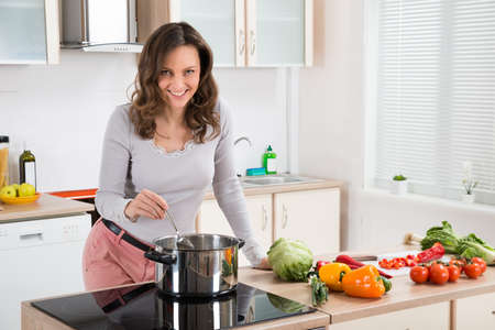 Young Woman Standing Near The Induction Cooker Cooking Meal In Kitchen