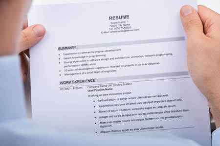 over the shoulder view: Close-up Over The Shoulder View Of Businessperson Reading Resume
