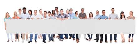Groep van stijlvolle professionele mensen uit het bedrijfsleven staan in een lijn met een lange lege banner voor uw reclame of tekst