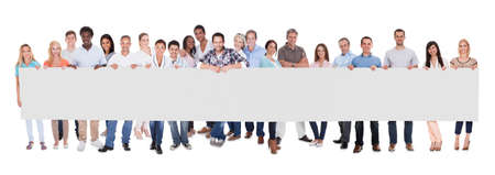Gruppe von stilvollen professionellen Geschäftsleuten stehen in einer Linie hält eine lange leere Banner für Ihre Werbung oder Text Standard-Bild
