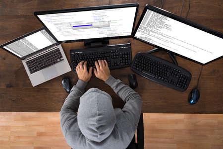 デスクのコンピューターから情報を盗むハッカーのハイアングル