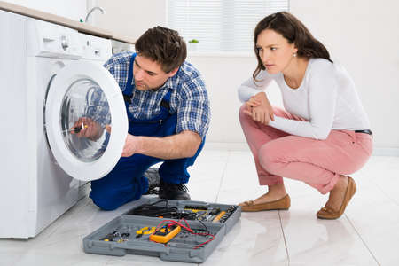Repairman Repairing Washer In Front Of Young Woman In Kitchen At Home