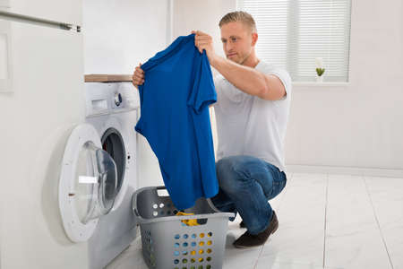 man machine: Young Man Looking At T-shirt While Using Washing Machine Appliance In Kitchen