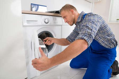 Young Male Technician Making Washing Machine In Kitchen