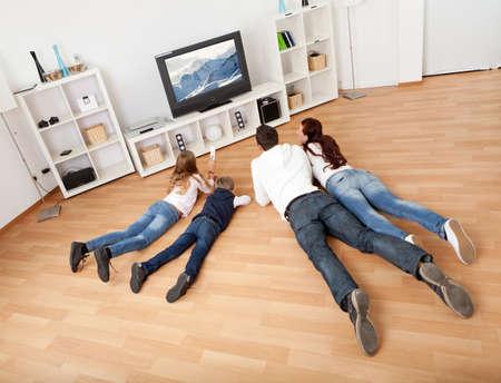 Joven de la familia viendo la televisión juntos en casa Foto de archivo
