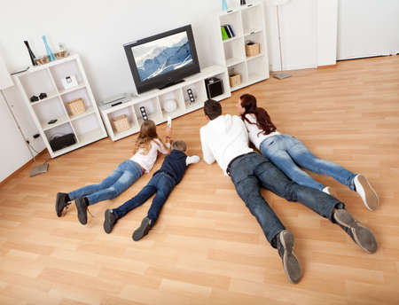 family sofa: Young family watching TV together at home