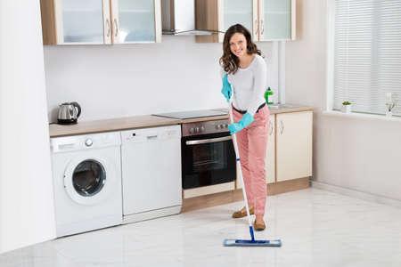 mujer limpiando: Mujer feliz con la fregona del piso de limpieza en la cocina en el hogar Foto de archivo
