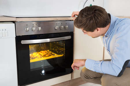 baking oven: Young Man Baking Bread In Oven Appliance At Home