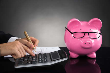 Close-up Van Businessperson Met Piggybank berekenen Tax Bij Bureau Stockfoto