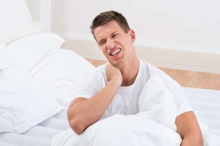 cansancio: Hombre joven que sufre de Dolor de cuello En Dormitorio