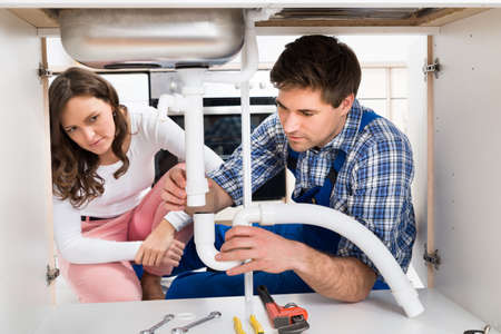Young Woman Looking At Male Worker Fixing Pipe View From Under The Kitchen Sink Stock Photo
