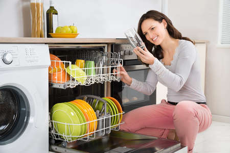 routine: Young Beautiful Woman Taking Drinking Glass From Dishwasher In Kitchen Stock Photo