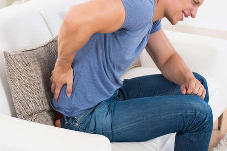dolor de espalda: Hombre joven en el sofá que sufre de Backpain En Casa Foto de archivo