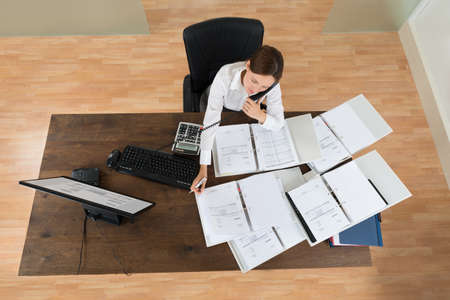 attending: High Angle View Of Young Businesswoman Attending Call While Calculating Finance At Desk Stock Photo