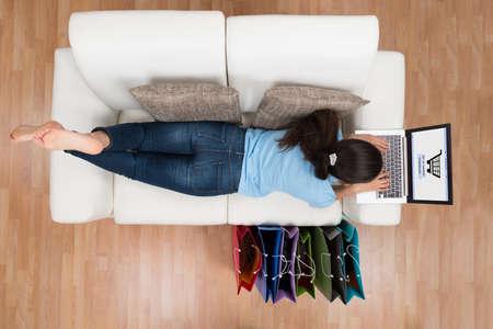 vysoký úhel pohledu: Vysoký úhel pohledu na mladé šťastná žena na pohovce nakupování on-line notebooku