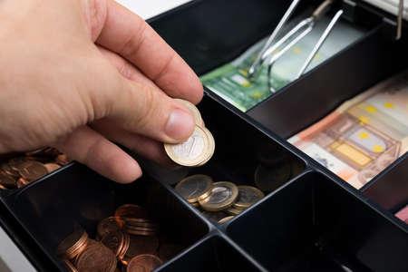 efectivo: Primer plano de la persona Manos poner monedas en la caja registradora