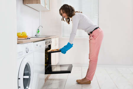 putting in: Young Beautiful Woman Putting Bread In Kitchen Oven