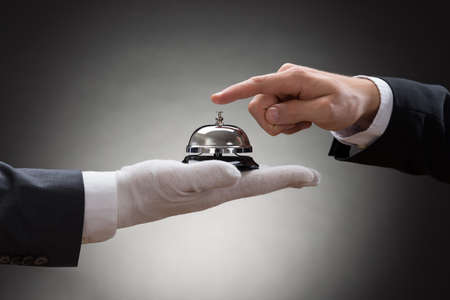 Close-up Of A Person's Hand Ringing Service Bell Hold By Waiter Banco de Imagens