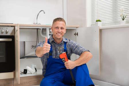 fontanero: Feliz fontanero joven con la llave ajustable que se sienta en la cocina de la habitación Foto de archivo