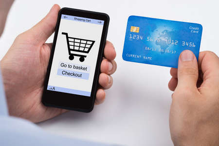 business credit application: Close-up Of Person Shopping Online With Credit Card On Mobile Phone