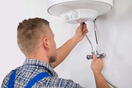home maintenance: Young Male Worker Fixing Electric Boiler With Screwdriver