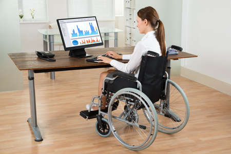 wheelchair access: Young Businesswoman On Wheelchair Analyzing Graph On Computer In Office