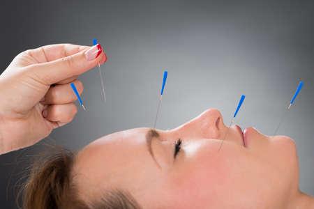 若い女性の顔に鍼を入れてクローズ アップ人手